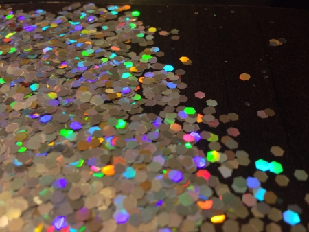 reflective: Close up rainbow hologram glitter texture on black background