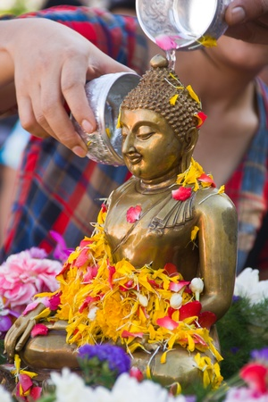 water pouring to Buddha statue in Songkran festival tradition of Thailand , to continue the tradition.