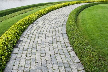 arcos de piedra: El bloque de piedra a pie camino en el parque con el fondo de hierba verde Foto de archivo