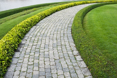 brick road: The Stone block walk path in the park with green grass background
