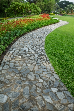 the stone block walk path with green grass and flowers background