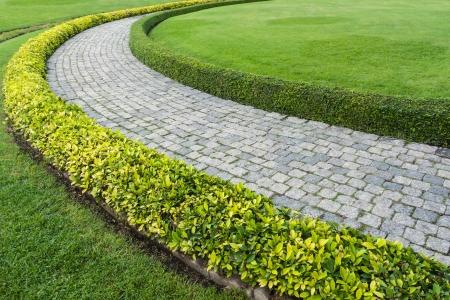El camino a pie de bloques de piedra con hierba verde