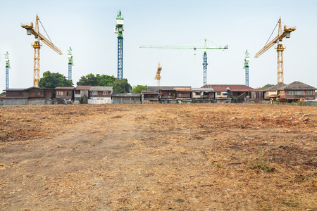 vacant land: crane construction in front of the village with vacant land