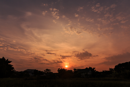 faintly visible: sunrise with clouds over the village