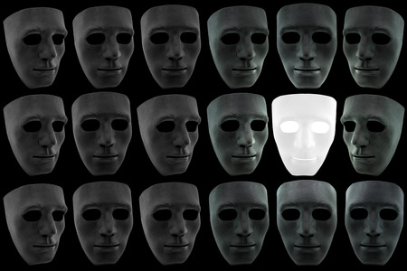 goodness: The white mask is surrounded by many black masks but also provides brightness around the sides, concept of goodness continues to endure and illumine in the midst of bad situations Stock Photo