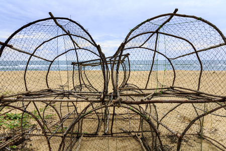 basket fish trap catch crabs, lobsters fishes on the sandy beaches Stock Photo