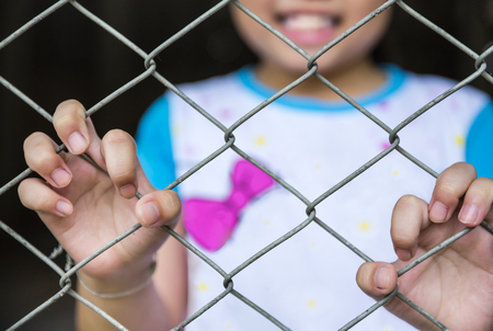 single girl child holding the cage stood smiling because she was free and very happy Stock Photo