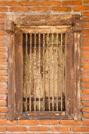 Janela de madeira antiga e barras de ferro na parede de tijolos como fundo e textura