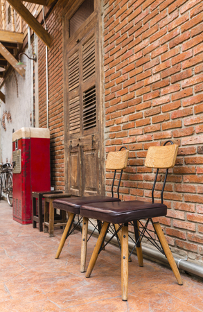 penthouse: Steel frame chairs are padded with brown cushions and a wooden backrest is placed in front of the brick wall