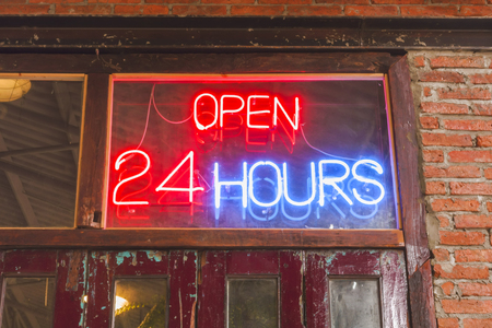 Close up open 24 hours sign on the old crimson door with brick wall Stock Photo