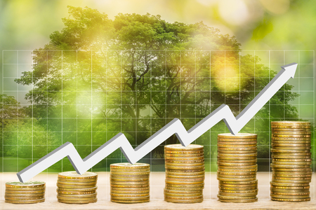 Double exposure of financial graph chart and rows of coins with white arrow indicates economic upturn and graph and blurred natural background, concept of natural economy and finance