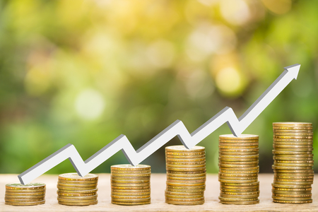 One dollar coins stack arranged as a graph with white arrow indicates economic upturn and blurred natural background, concept of natural economy and finance Stock Photo