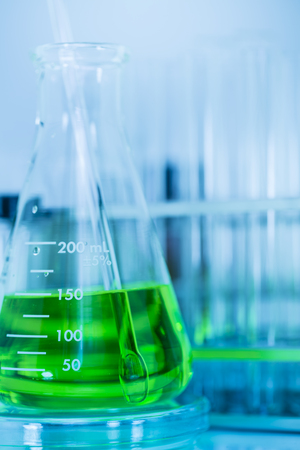 Laboratory glass Erlenmeyer flask has green chemical solution and glass rod with test tubes in test tube rack, science background Stock Photo