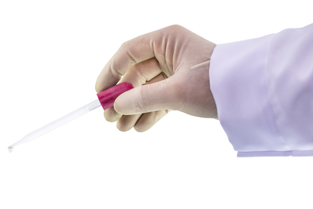 Chemist hand holding a pipette dropping with emerging drop of chemical solution isolated on white background