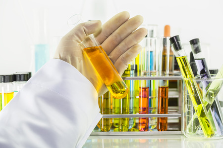 Chemist hand holding a test tube with a orange chemical solution and laboratory glass test tubes and chemical vials with colorful chemical solution behind the scenes, science background Stock Photo