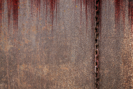 Bloody background scary old rusty chains hanging on rusted steel wall, concept of horror and Halloween Banco de Imagens