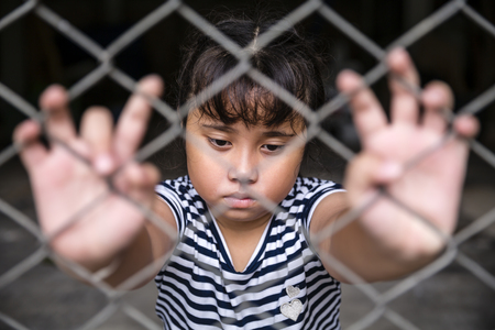 incarcerated: Single sad Asian girl child holding the cage was imprisoned make no freedom or lack of freedom