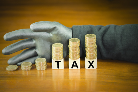 Coins stack on top of word tax on wooden block with thieves wear black gloves, concept of tax evasion avoidance