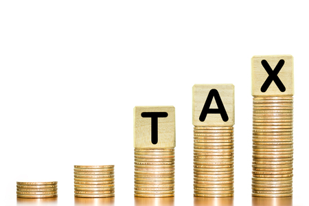 Word tax wooden block on the money coins arranged as a graph on wooden table on white background, concept of the increasing of tax