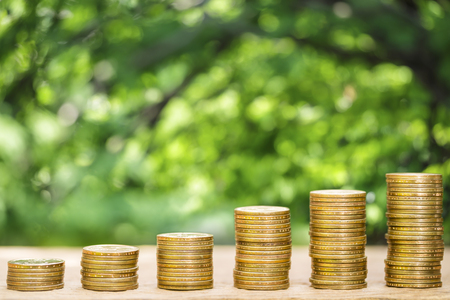 Money coins arranged as a graph on wooden table with natural bokeh background, concept of business growth and saving money