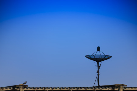 Black satellite dish on the roof of the blue sky, concept of communication technology network