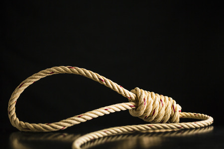 Brown rope noose dark and light on black table with black background, concept of hanging suicide Stock Photo