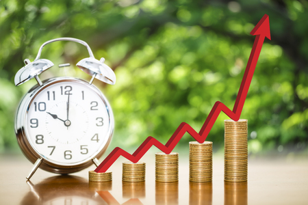 Stack of money coins arranged as a graph with red arrow indicates economic upturn and alarm clock on wooden table with blur nature background, concept of time to money growth and finance