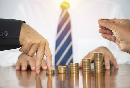 Businessman fingers hand step forward on stack of money coins arranged as a graph on wooden table with man hand holding putting on stack of money coin