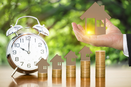 Businessman hand holding money coin with wooden toy house putting on stack of money coins on wooden with alarm clock and blurry nature background Imagens