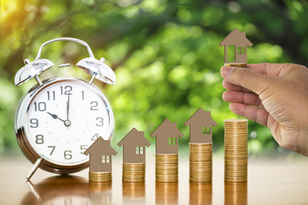 Man hand holding money coin with wooden toy house putting on stack of money coins on wooden table with alarm clock and blurry nature background