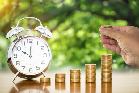 Money coin stack arranged as a graph on wooden table and alarm clock with businessman hand holding stack of money coin and blur nature background