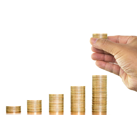 Money coins stack arranged as graph with man hand holding putting on stack of money coin on white background, concept of money growth and save money