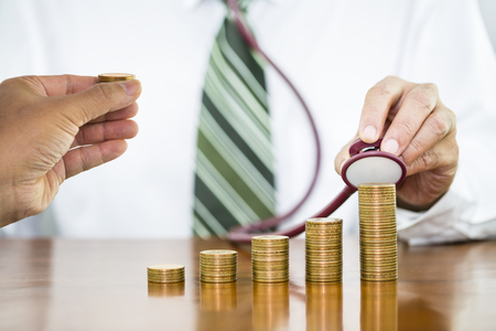 Businessman hand holding stethoscope checking stack of money coins arranged as a graph with man hand holding putting on stack of money coin
