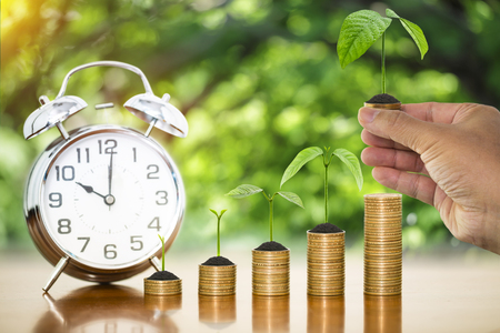 Money growing plants on money coins stack arranged as graph with alarm clock and businessman hand holding money coin with tree growing putting on stack of money coin Imagens