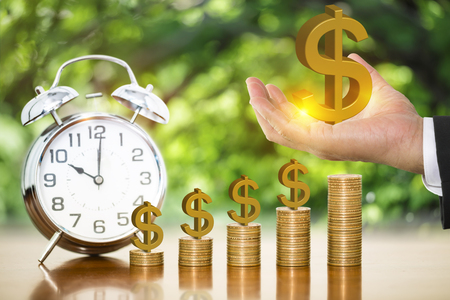 Businessman hand holding golden dollar sign putting on stack of money coins on wooden table with alarm clock and blurry nature background, concept of time to money growth and saving money