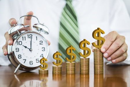 Businessman hand holding golden dollar sign on dollar coin putting on money coin stack arranged as a graph with alarm clock, concept of time to money growth and saving money