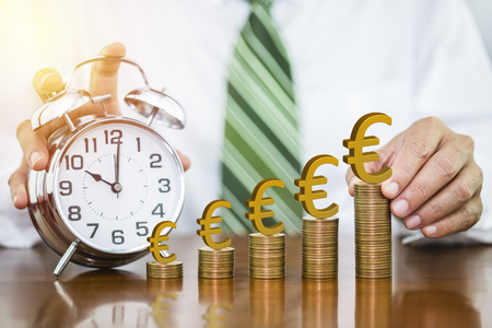 Businessman hand holding golden euro sign on money coin and putting on money coin stack arranged as a graph with alarm clock, concept of time to money growth and saving money Imagens