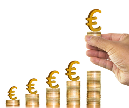 Businesman hand holding golden euro sign on money coin and putting on money coin stack arranged as a graph on white background, concept of money growth and saving money