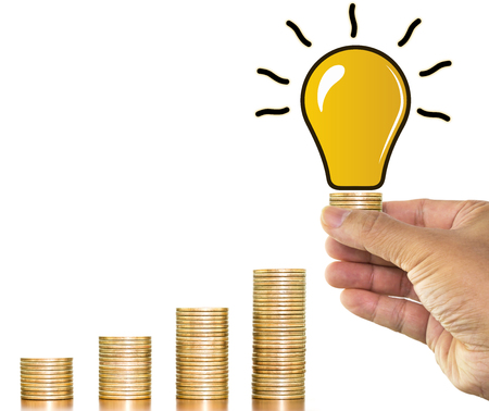 Man hand holding stack of money coins with light bulb ideas over money coin stack arranged as a graph on white background, concept of financial planning and save money Imagens