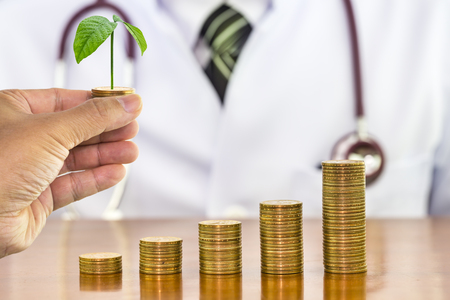 Man hand holding money coin with tree growing and blurry the doctor stethoscope around neck a scene in the back, concept of financial health with medical expenses and saving money Imagens
