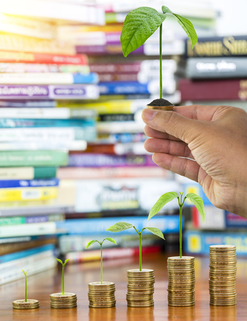 Man hand holding tree growing and soil on money coins stack arranged as a graph with blurred pile of book as background, concept of educational advancement and saving money Imagens