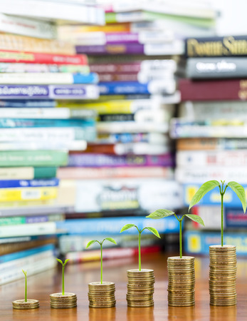 Tree growing on money coins stack arranged as a graph with blurred pile of book as background, concept of educational advancement and saving money