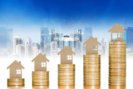 Wooden toy house putting on money coins stack arranged as a graph with blurred cityscape background; concept of money growth and saving money Imagens