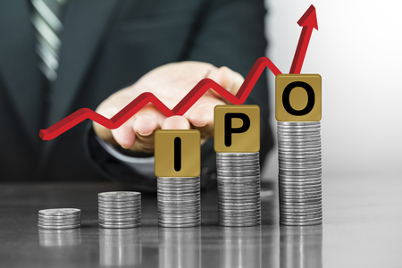 Businessman hand holding red arrow up with the letters IPO on money coin stack arranged as a graph, concept of Increased investment
