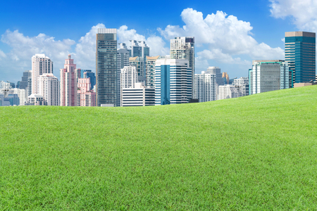 Green lawn outside the big city with cloud and blue sky Editorial