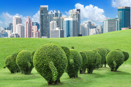The tree is trimmed to the shape of elephants on green lawn outside the big city to add oxygen to the city, concept of save the earth and environment with environmental protection trap