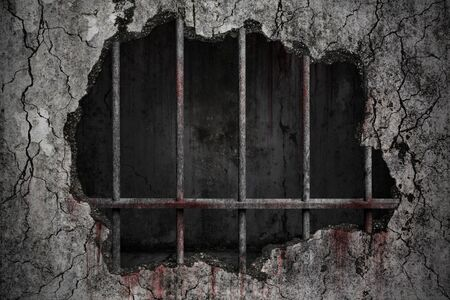Bloody background scary damaged grungy crack and broken concrete wall with old prison metal bars, concept of strengthen and protect with horror