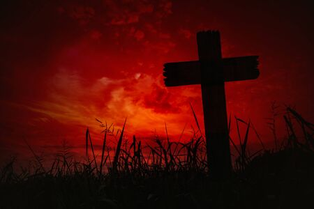 Scary background cemetery cross with dark silhouette in twilight sky, concept of horror and Halloween