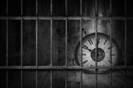 Distorted soft melting clock is imprisoned in old prison rusted metal bars with dark and dim light, concept of losing valuable time and trap in business Stock Photo