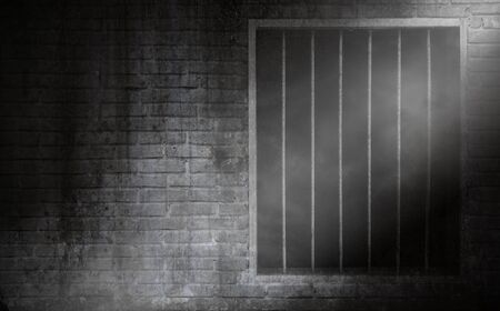 Light beam with smoke on prison window with rusty bars and old brick prison cell wall Stock Photo